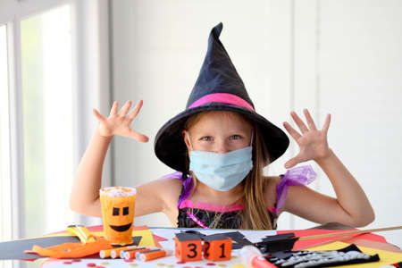 A little girl in a witch costume in a medical mask makes crafts and scares. Halloween with safety measures from Covid-19 Reklamní fotografie
