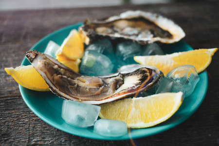 Close-up of fresh open raw oysters on a blue plate, with lemon and ice. Healthy seafood. View from above. Seafood. Gourmet food.