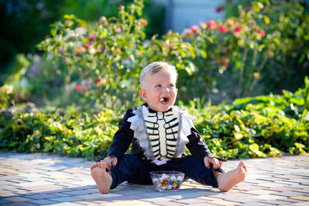 A little boy sits on the grass in a skeleton suit and eats sweets. Halloween holiday. Copy space