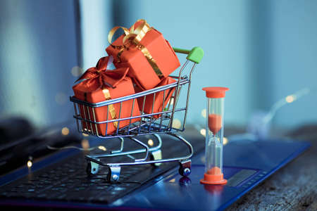 Hourglass and small basket with boxes of Christmas gifts on the background of a laptop. Online shopping. Boxing day concept. Have time to buy. Sales. Copy space.