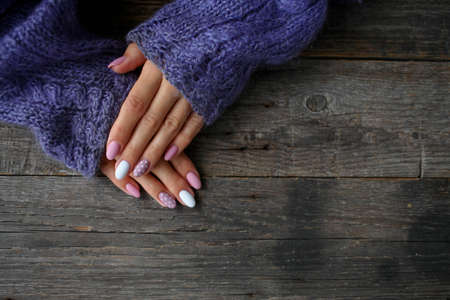 Women is hands with a beautiful manicure, in a knitted sweater on a wooden background in. Autumn trend, polish beige and white polka dots on nails with gel polish, shellac. Copy space.