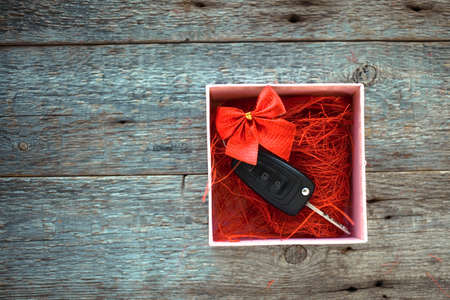 Car key in a gift box with a red ribbon bow on a wooden background. Gift for Christmas or Valentine is Day or present an abstract concept. Copy space.