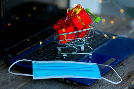Small basket with boxes of Christmas gifts and a medical mask on the background of a laptop. Online shopping. Boxing day concept in the COVID-19 pandemic. Manage to buy. Sales. Copy space.