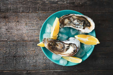 Close-up of fresh open raw oysters with lemon and ice on a blue plate against a wooden background. Healthy seafood. View from above. Copy space. Seafood. Gourmet food. 版權商用圖片