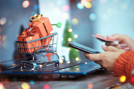 The girl presses her hand on the smartphone screen and holds a credit card in her hands. Trolley with gifts on the background of a laptop. Online shopping from home. Christmas and New Year sales