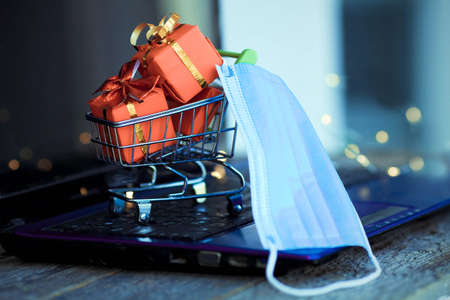 Small basket with boxes of Christmas gifts and a medical mask on the background of a laptop. Online shopping. Boxing day concept in the COVID-19 pandemic. Manage to buy. Sales.