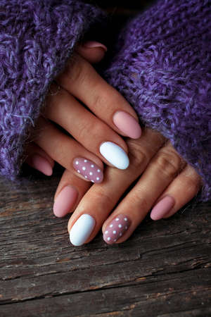 Women is hands with a beautiful manicure, in a violet knitted sweater on a wooden background in. Autumn trend, polish beige and white polka dots on nails with gel polish, shellac. Close up.
