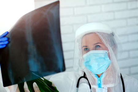 The doctor in PPE looks thoughtfully at the X-ray. Woman doctor in medical mask and protective suit works during a pandemic COVID -19.