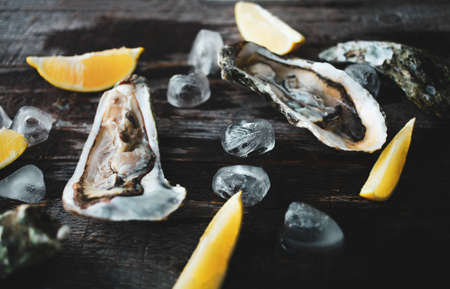 Close-up of fresh open raw oysters with lemon and ice on a wooden background. Healthy seafood. View from above. Copy space. Seafood. Gourmet food.