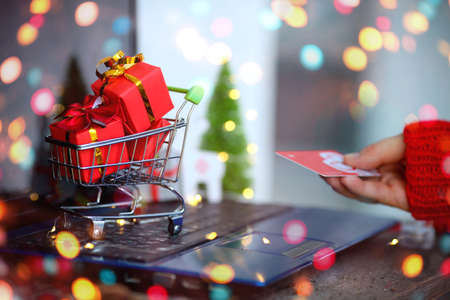 The girl holds a credit card in her hands. Trolley with gifts on the background of the laptop. Online shopping from home. Christmas and New Year sales