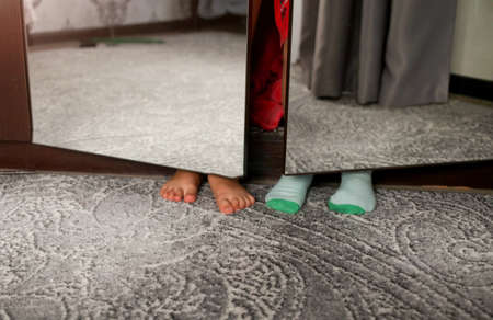 The children hid in a wardrobe with mirrored doors. Baby feet are visible behind the closet. Kids game. Fun. Humor. Cleaning 版權商用圖片