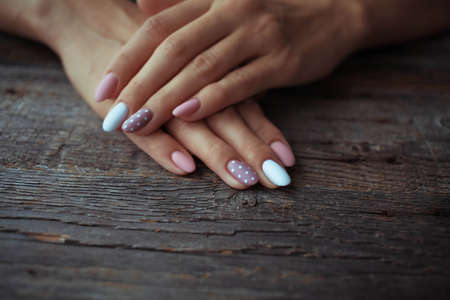 Women is hands with a beautiful manicure on a wooden background. Autumn trend, polish beige and white polka dots on nails with gel polish, shellac. Copy space.