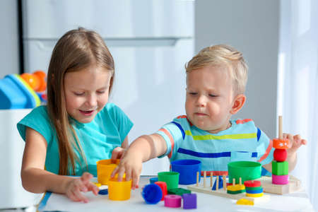Sister helps little brother to assemble the pyramid. Educational logical toys for children. Montessori games for child development. Little boy and girl play wooden toy.