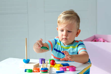 Little boy 2 years old is played with a wooden pyramid. Educational logic toys for children. Montessori games for child development. Copy space.