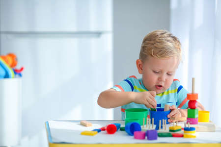 Little boy 2 years old is played with a colors toys. Educational logic toys for children. Montessori games for child development. Copy space.