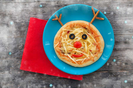 Christmas pizza in a shape of reindeer on a wooden background. Fun food for kids - cute deer. Stock Photo