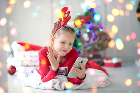 A little girl waves her hand and wishes a Happy New Year using a mobile phone for video calls to friends and parents.Christmas online holiday remote celebration X mas in lockdown coronavirus