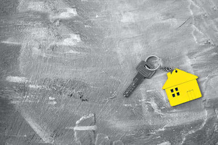 Keys about a charm of the house of yellow color on a gray background. Top view.Color of the year 2021 Ultimate Gray and Illuminating. Copy space. Main color trend concept.