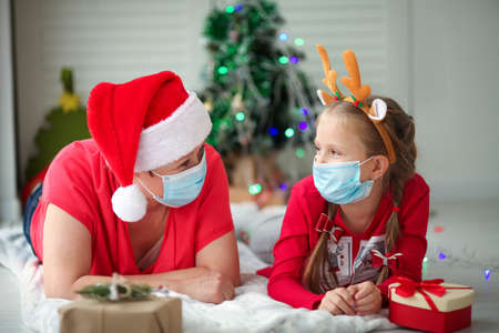 Grandmother and granddaughter in medical masks look at each other under the Christmas tree. Family traditions. Christmas amid the covid-19 pandemic.