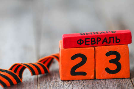 Wooden calendar with the date February 23 and george ribbon. Fatherland defender day. Father day. Men is day in Russia, Belarus, Tajikistan, Kyrgyzstan. Text in Russian February 23. Copy space.
