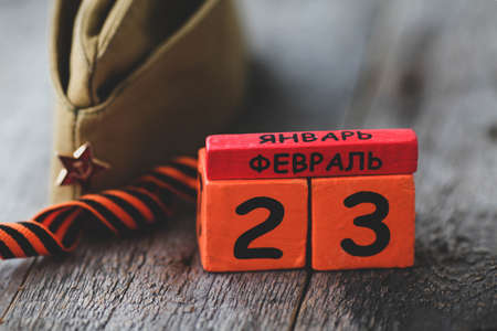 Wooden calendar with the date of February 23, St. George ribbon, garrison cap. Defender of the Fatherland Day. Men day in Russia. Text in Russian on February 23.