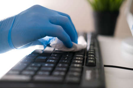 Male hands in rubber gloves wipe the keyboard from the computer. Disinfection in the office during COVID-19