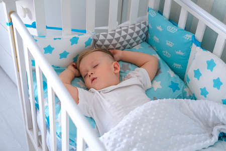 A charming boy sleeps in a baby white crib. A small child sleeps in a crib on blue bedding. Sleep workout concept.