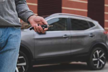 Man in front of the new car and holding keys. Salesman is carrying the car keys delivered to the customer at the showroom with a low interest offer. Rent, credit, insurance, car purchase. Copy space