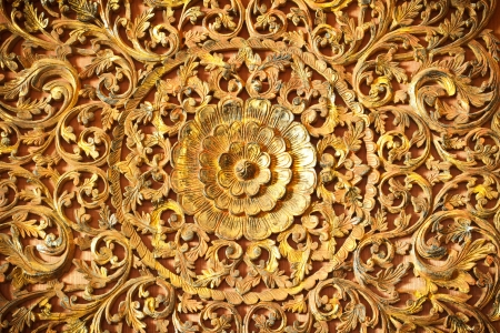 Thai flower carved natural paint on temple wooden door photo