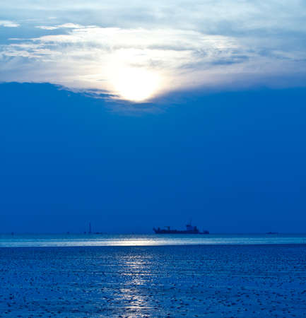 Blue sea with ocean liner at sunset photo