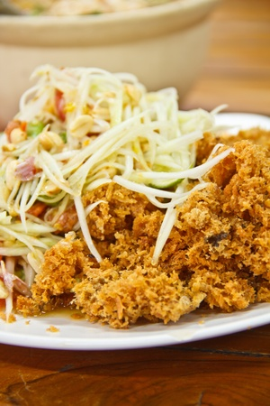 Green papaya salad and fried catfish is delicious Thai food  photo