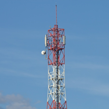 Red and white roof top cellular tower under blue sky Stock Photo - 16812698
