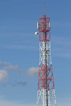 Red and white roof top cellular tower under blue sky Stock Photo - 16812684