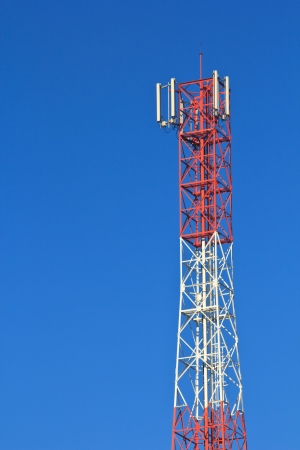 Red and white roof top cellular tower under blue sky Stock Photo - 16812690