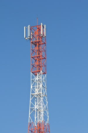 Red and white roof top cellular tower under blue sky Stock Photo - 16812685