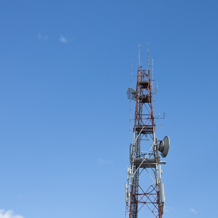 Red and white roof top cellular tower under blue sky Stock Photo - 17297106