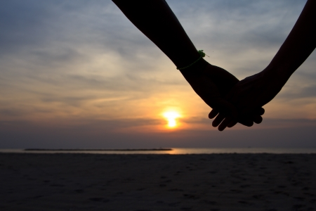 Silhouette hand in heart shape with sunrise in the middle and beach background photo