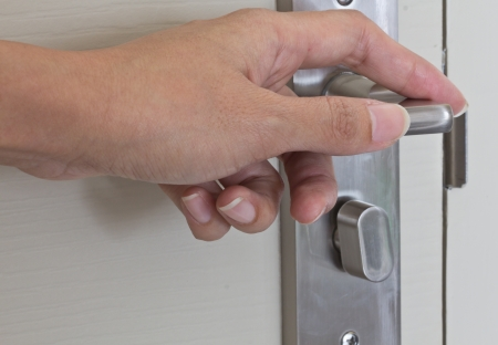 Locking up or unlocking door with hinge in hand photo