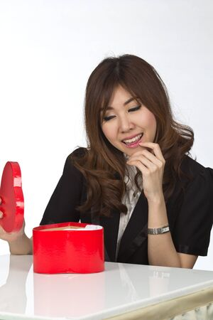 Attractive Asian Mixed Women finding out what is inside the gift box photo