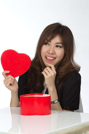 finding out: Attractive Asian Mixed Women finding out what is inside the gift box Stock Photo