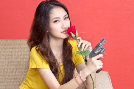 Young asian cute woman with handgun photo