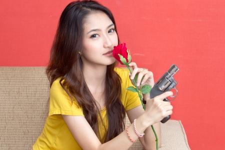 Young asian cute woman with handgun