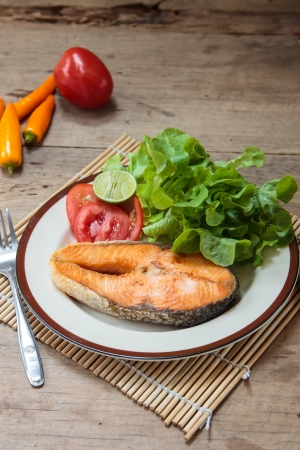 salmon steak with lime on white plate photo