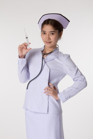 Beautiful Asian doctor or nurse preparing a vaccination photo
