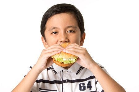 Little boy eating a hamburger. isolated on a white background photo