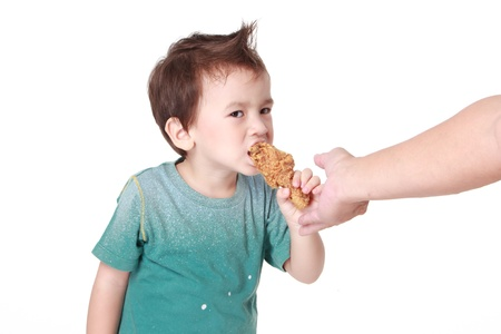 Eating Chickenchild eating a chicken leg on white background