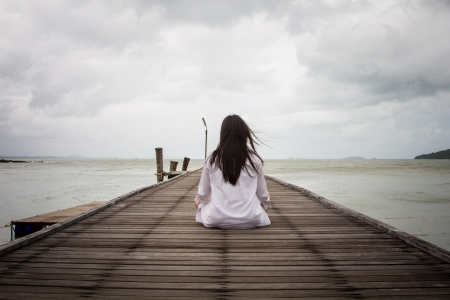 dhyana: Meditation by young women in white dress on a bridge by the sea. Stock Photo