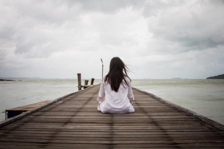 Meditation von jungen Frauen im weißen Kleid auf einer Brücke direkt am Meer. Standard-Bild - 20733013