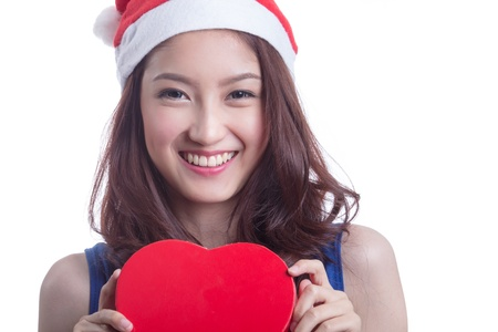 beautiful woman with a christmas hat and carrying a chocolate box with the shape of a heart Stock Photo - 20901665