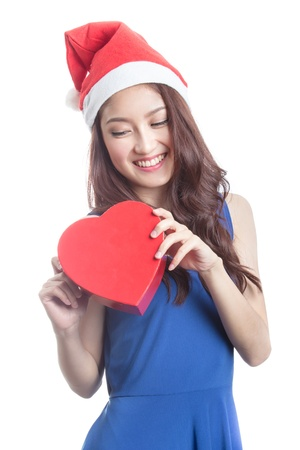 beautiful woman with a christmas hat and carrying a chocolate box with the shape of a heart photo